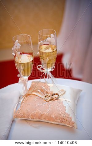Two Wedding Rings On A Cushion On The Background Glasses Of Champagne