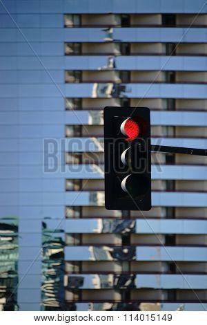 Traffic light in front of modern skyscraper
