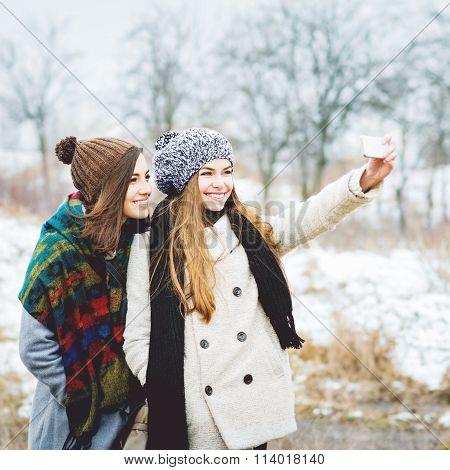 Happy teenage girls taking a selfie in winter