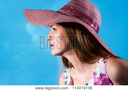 Beautiful Girl In A Pink Hat From The Sun In A Profile On A Blue Background