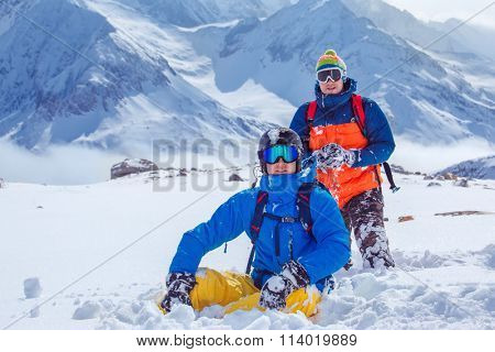 Friends in snowboard outfit playing snowballs in winter mountains