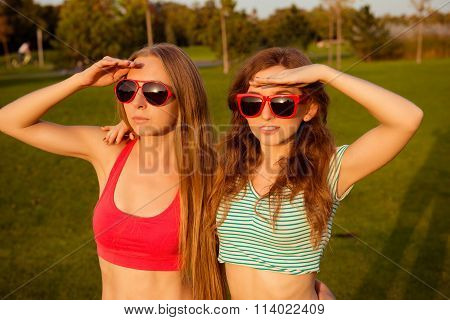 Two Young Slender Girls With Glasses Watching Sunset In The Park
