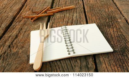 Blank earth tone note book and wooden fork with cinnamon on old dark brown wooden planks