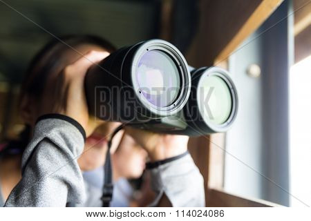 Woman use the binoculars for birdwatching