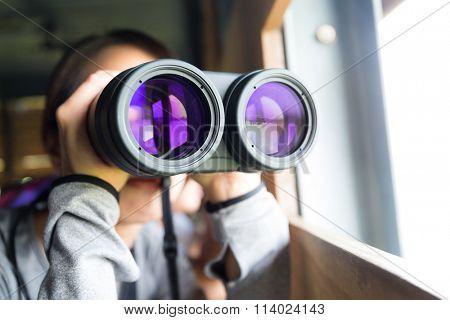 Woman looking though binoculars for birdwatching