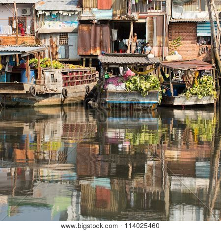 HO CHI MINH, VIETNAM - JAN 10, 2015: Floating market with reflection in water. Is located in the South of Vietnam, is the country's largest city, population 8 million.