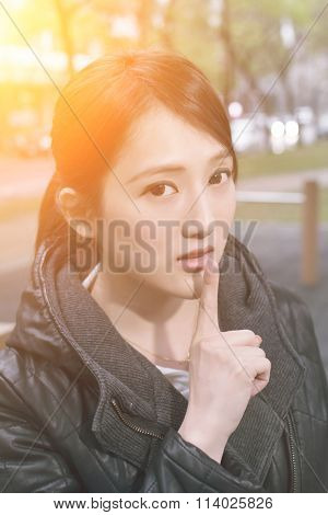 Asian young woman give you a gesture of silent, closeup portrait.