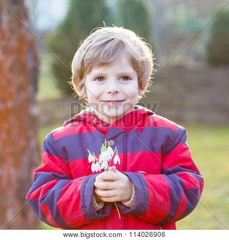 little kid boy in red jacket holding snowdrop flowers