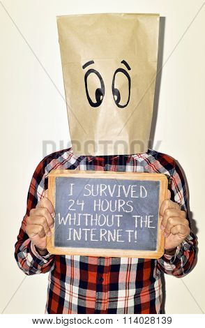 a young caucasian man with a paper bag with a funny face in his head shows a chalkboard with the text I survived 24 hours without the internet