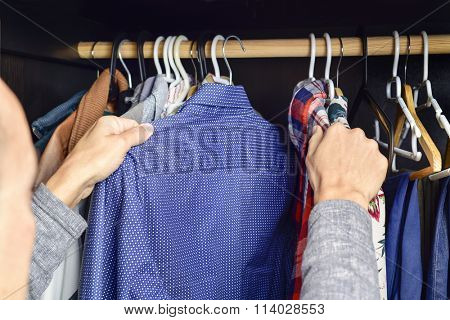 closeup of a young caucasian man choosing a shirt from a clothes rack