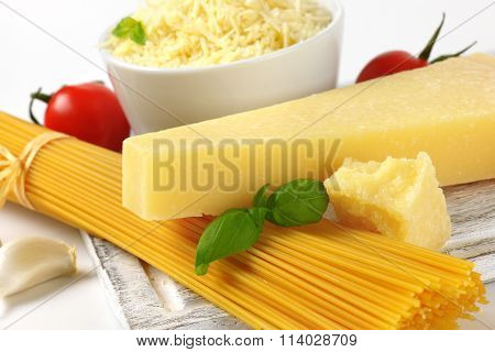 detail of fresh parmesan cheese, vegetable garnish and bundle of raw spaghetti on wooden cutting board
