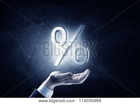 Businessman hand holding blue crystal ball with percent sign.