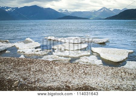 Melt The Ice In The Ocean On A Background Of Mountains