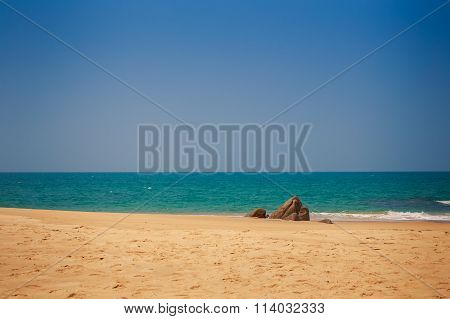 View Of Sand Beach With Stone Against Azure Sea With Wave Surf