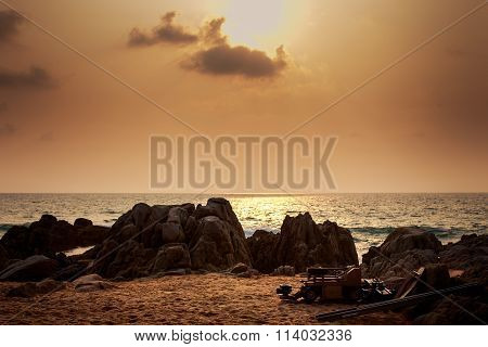 Sunlight From Behind Clouds With Rocks Boat On Foreground