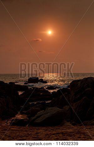 Sun Disk Over Sea At Sunrise Dark Rocks On Foreground