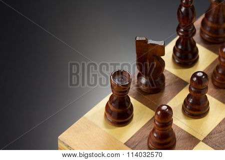 chess figures and board at black background