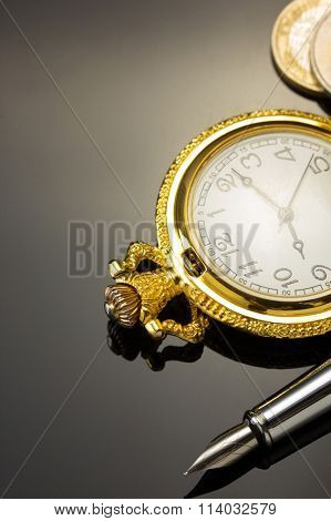 ink pen and pocket watch on black background