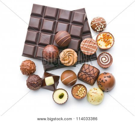 various chocolate pralines and chocolate bar on white background