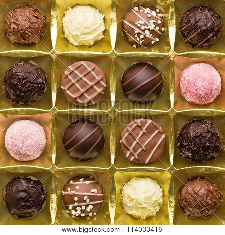 various chocolate pralines in golden box