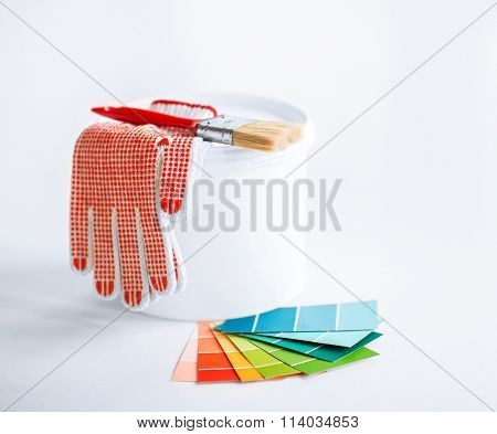 paintbrush, paint pot, gloves and pantone samplers