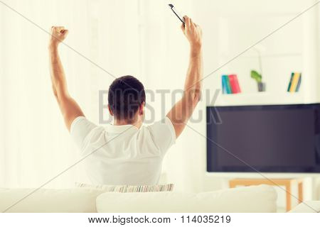 man watching tv and supporting team at home