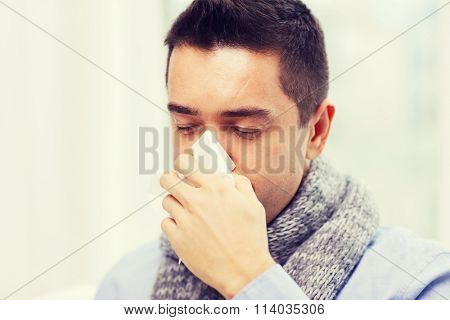 close up of ill man with flu blowing nose at home