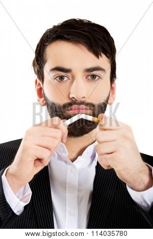 Businessman breaking a cigarette.