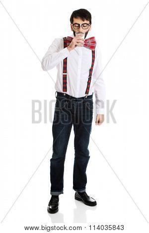 Man wearing suspenders drinking milk.