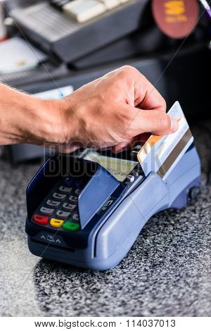 Credit card payment at terminal in shop