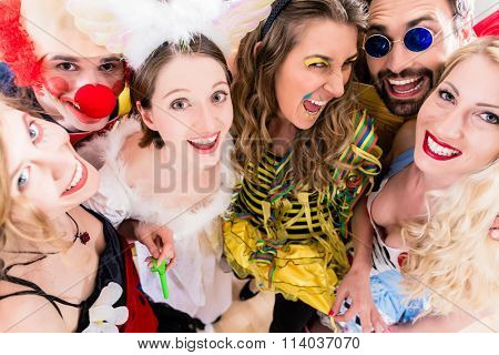 Women and men celebrating at party for new years eve or carnival