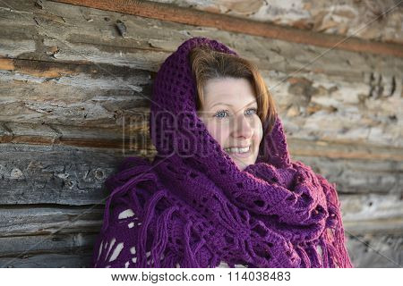 The Russian Woman In  Shawl Warms Hands Near An Izba