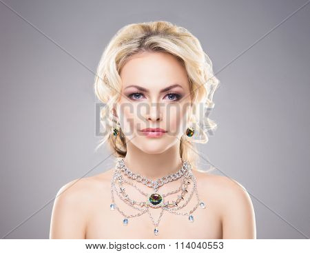 Portrait of gorgeous blond wearing luxury necklace with a gem over grey background.