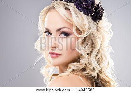 Close-up of absolutely gorgeous model with pure skin and bare shoulders wearing purple flower alike crown over grey background.