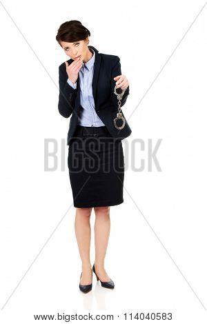 Businesswoman holding metal handcuffs.