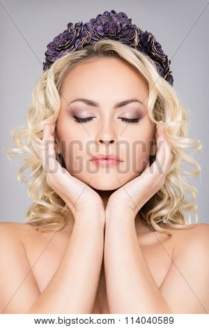 Close-up of gorgeous blond with pure skin and bare shoulders wearing purple headband over grey background.