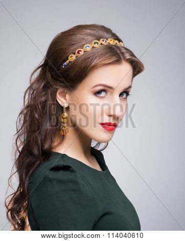 Close-up of gorgeous, young brunette with enigmatic face wearing luxury golden headband and earrings over isolated background.