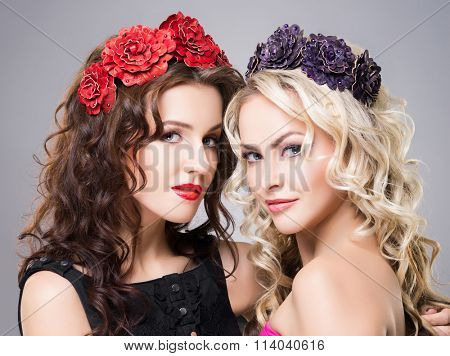 Close-up of two attractive, young ladies wearing flower alike accessories over grey background.