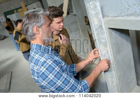 Man using a straight edge to check levelness