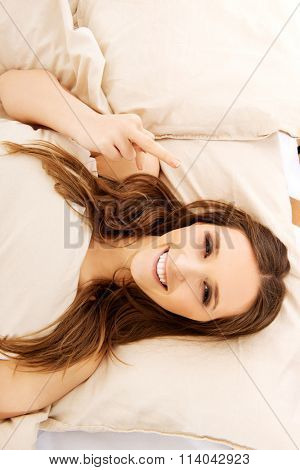 Woman showing middle finger in bedroom.