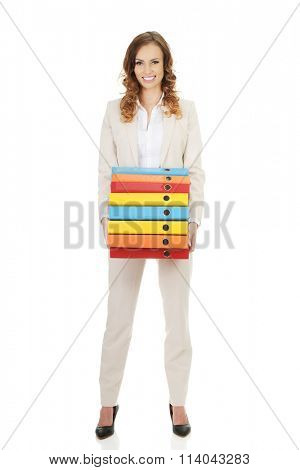 Female carrying heavy binders against.