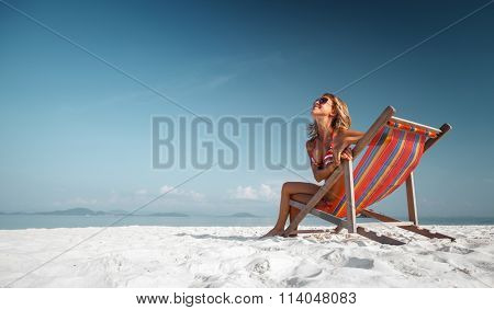 Young lady relaxing in the chair on a tropical beach with white sand
