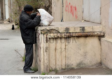 Homeless man looking for food in rubbish