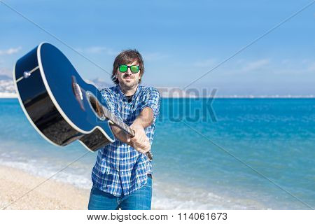 Bearded Man In Sunglasses With Guitar On Beach