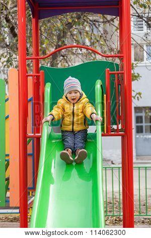 Happy Boy Sliding Down On Playground