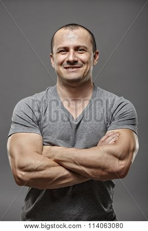 Muscular Man With Arms Crossed Isolated On Gray