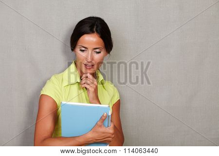 Pensive Woman With Hand On Chin Holding Tablet