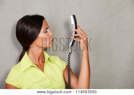 Charismatic Female Kissing While Holding Phone