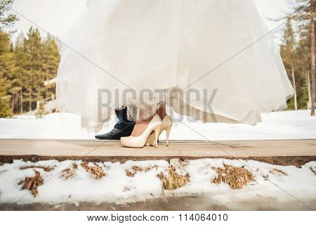 Legs newlyweds on wooden bridge  in winter wedding day