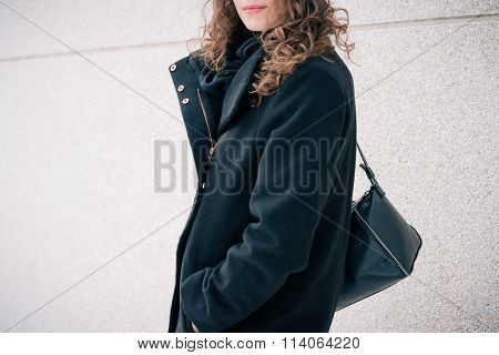 Girl In Black Coat And With The Purse On Her Shoulder Walking Down The Street And Turned To Look At
